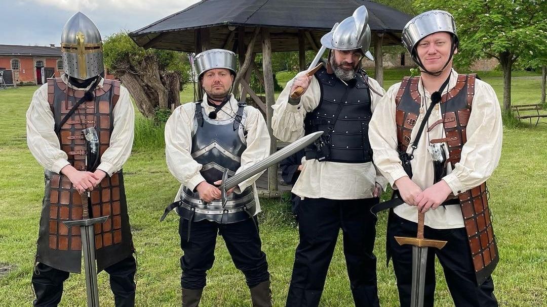 Die Teilnehmer mit Schwertern in voller Rüstung
